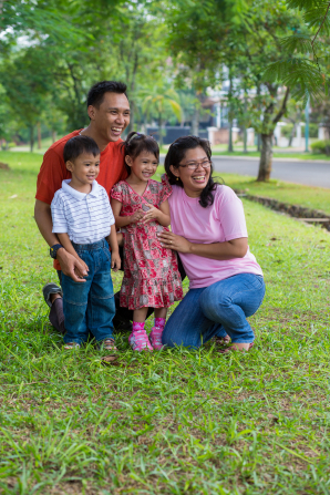 A mother and father stand on the grass and smile with their two children.