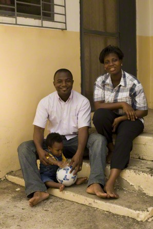 A husband and wife sit on the steps with their toddler, who is playing with a ball.
