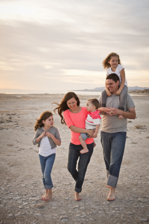 A father walks on the beach with his daughter on his shoulders. His wife is holding their baby, and another daughter is walking nearby.