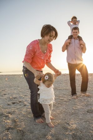 A mother holds her baby daughter's hands while walking on the beach with her husband and other child.
