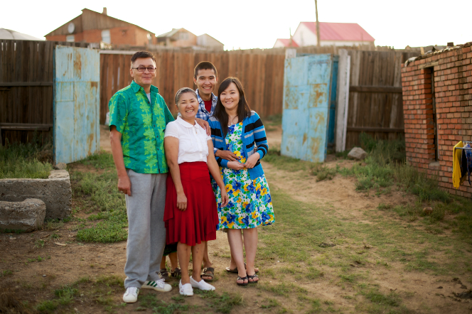 A father in Mongolia and his three adult children posing together outside, with a wooden fence and houses in the background.