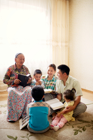 A family sits in a circle on the carpet and reads the scriptures together.