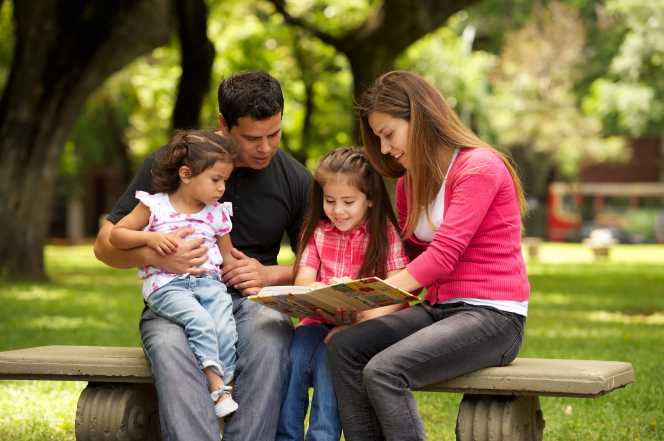 A mother and father sit on a bench with their two children and read a book to them.