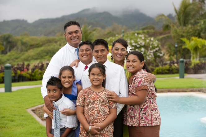 A family of eight huddling together on a stormy day in Hawaii to smile for an informal family photograph.
