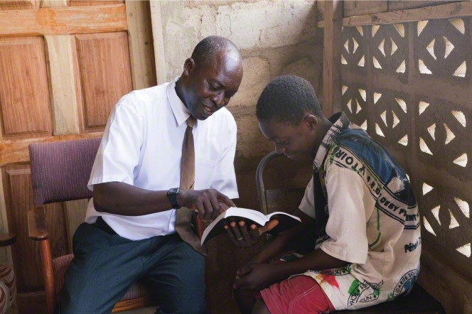 A father sits outside with his son and reads the scriptures with him.
