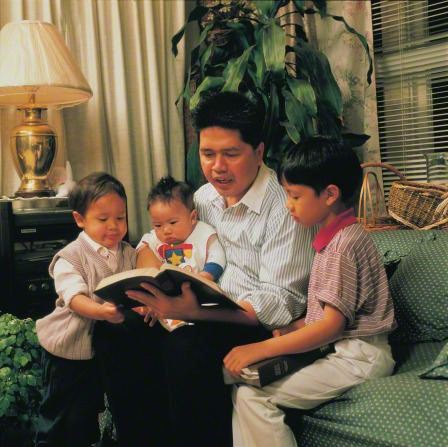 A father sits on a couch with his three young children around him and reads them a book.