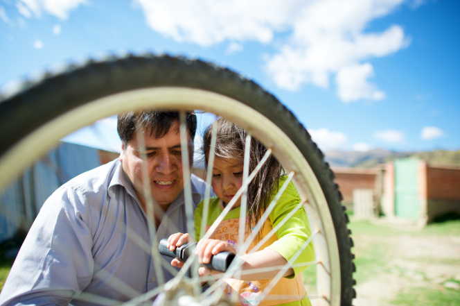 A man holds his daughter while helping her to repair a bike tire that is partially obscuring the view of their faces.