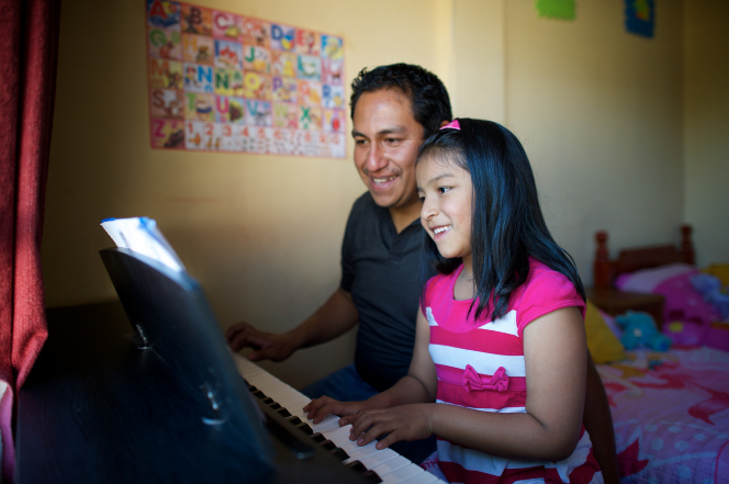 A man in a black shirt sits next to his young daughter, who is wearing pink stripes, while the two of them play the piano together.