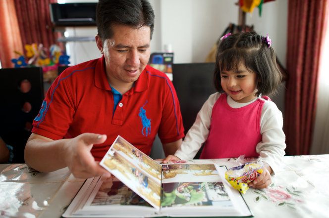 A father sits next to his daughter at a table and shows her pictures in a family photo album.