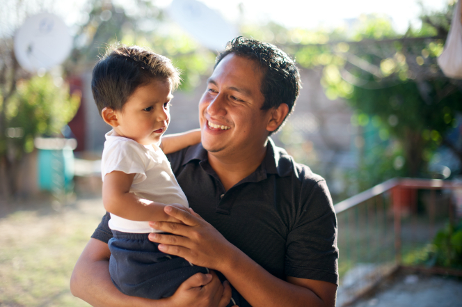 A man in a black shirt holds and smiles at his infant son, who is wearing a white T-shirt and looking to the side.