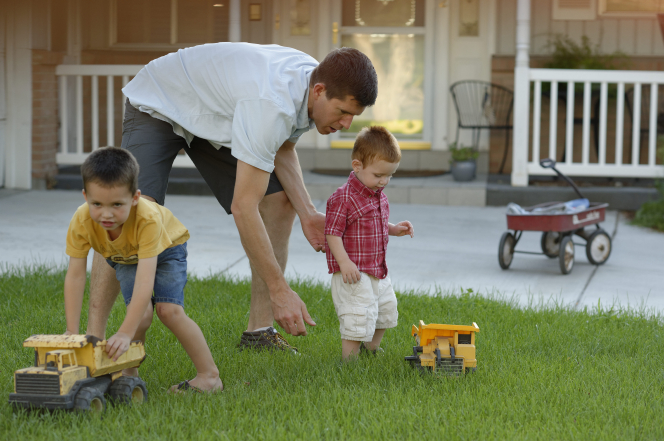 A father plays with his two young sons outside in the yard with toy trucks.