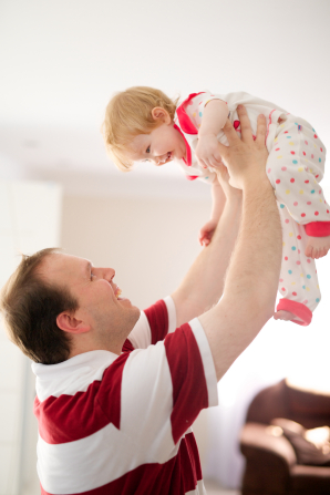 A man in a red and white striped shirt holds his baby girl high above his head and looks up at her smiling face.