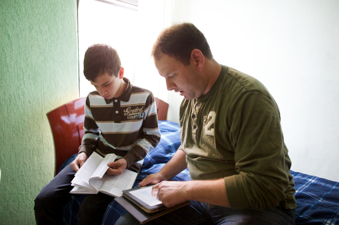 A man in a green shirt sits with his teenage son on the edge of a bed and reads from the scriptures on a tablet.