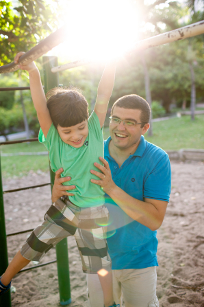 A man in a blue shirt holds his son up on some handlebars on a playground at a park.