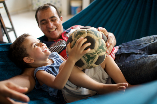 A man sits in a blue hammock with his young son who holds a worn soccer ball while the two of them talk and laugh.