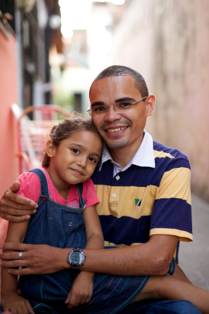 A man in a blue and yellow striped shirt holds his daughter, who is in a denim jumper, while the two of them smile at the camera.