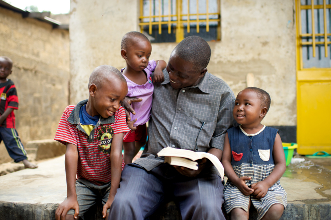 A father and his three young children in the Congo sit outside and open a set of scriptures together to read.