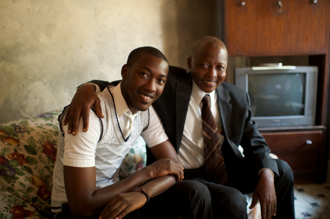 A father and an older son in the Congo sit indoors on a couch, smiling, to have a portrait taken.