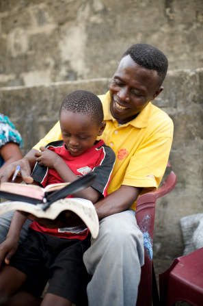 A father and his son in the Congo sit outside on lawn chairs and open the scriptures to read together.