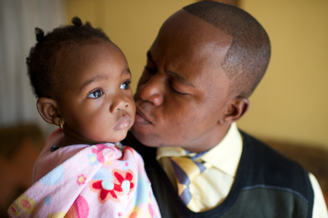 A father in the Congo kisses his infant daughter on the cheek while she stares off into the distance with a serious expression.