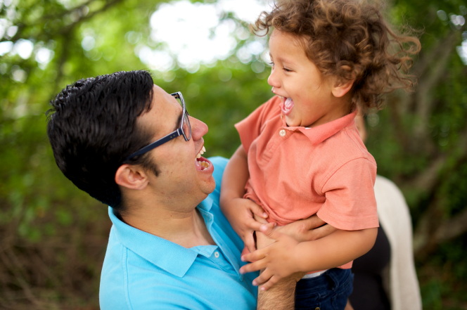 A father and his child pause to share a laugh while playing outside together on a sunny day.