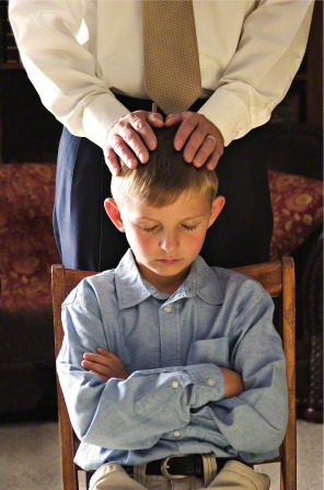 A father puts his hands on his son's head and gives him a priesthood blessing.