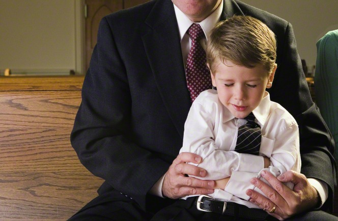 A father helps his son fold his arms and pray while they sit on a pew at church.