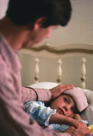 A father sits on the bed and puts his hand on his ill daughter's head.