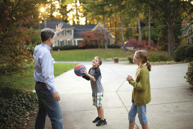 A father plays basketball in the driveway with his son and daughter.