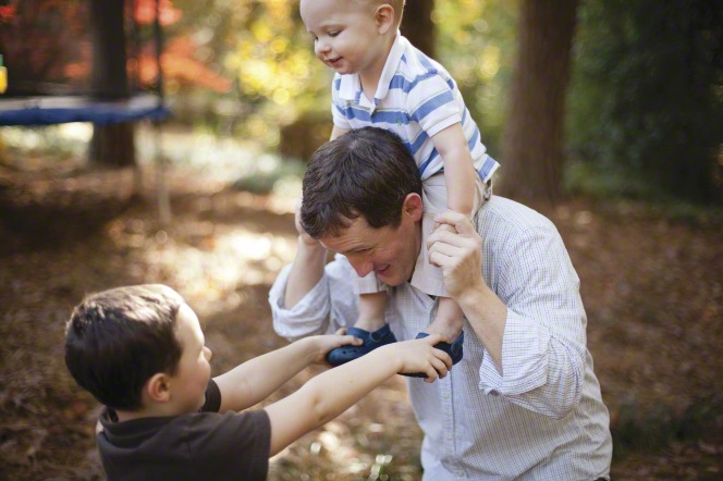 A father plays with two sons, one on his shoulders, in the park.