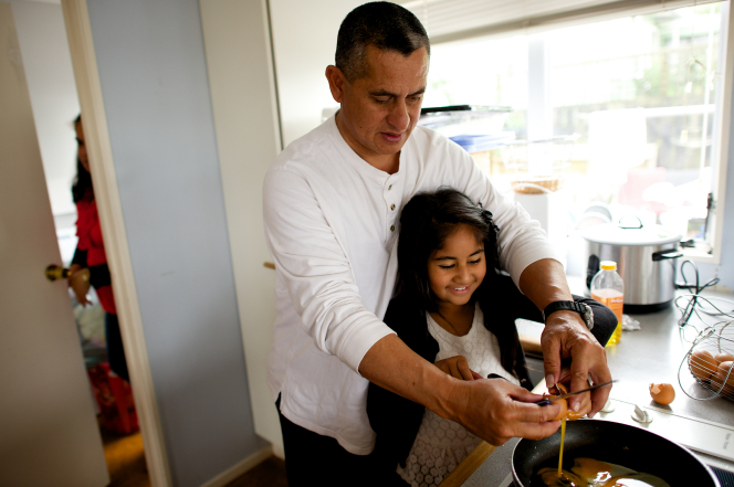 A father cracks an egg with his daughter over a skillet while they cook in the kitchen.