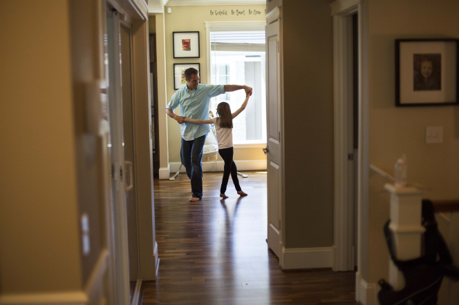 A father, wearing a blue shirt, and his daughter are seen from across the hall, dancing in their living room together.