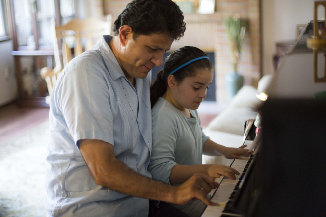 A father sits at a piano with his young daughter and plays with her.