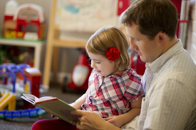 A father sits with his young daughter in a playroom and reads her a book.