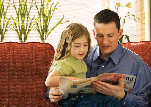 A father sits with his daughter on a couch and reads the Friend magazine to her.