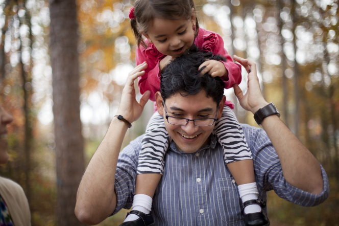 A toddler girl sits on her father's shoulders and smiles.