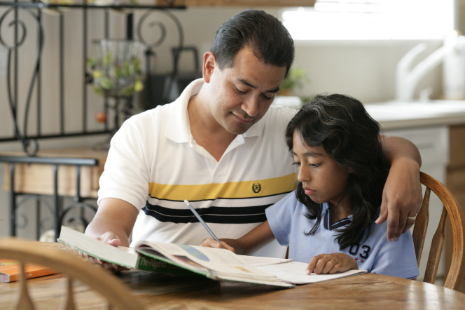 A father puts his arm around his daughter at the dining room table and helps her with her homework.