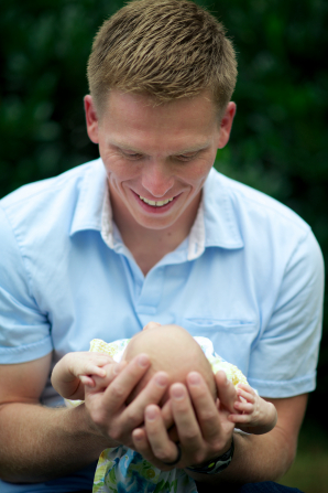 A father looks down with a smile and holds his newborn baby.