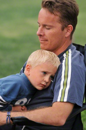A father puts his arms around his young son outdoors.