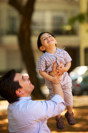 A father from Argentina lifts up his young son above his head while both smile.