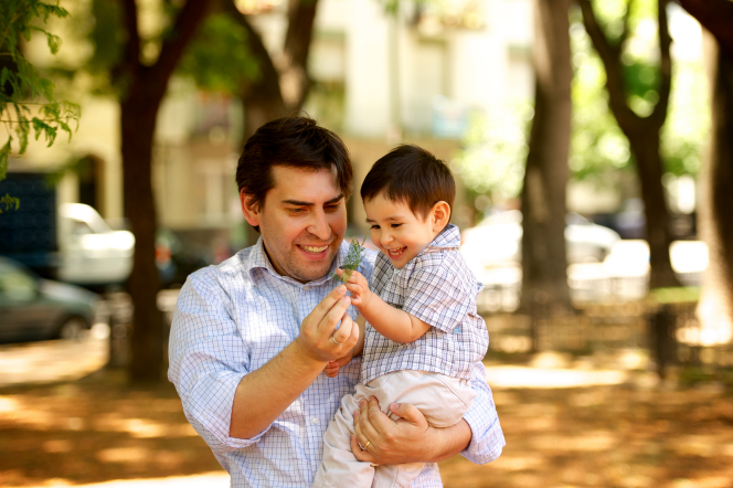A father holds his toddler son in the park and shows him a leaf.