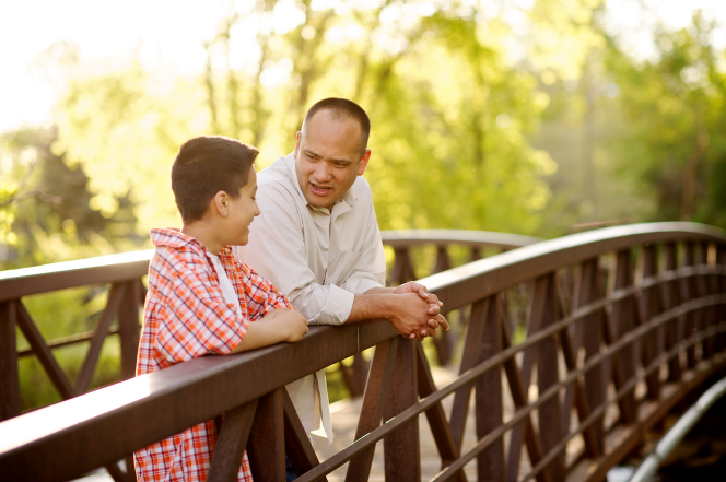 A father leans against a rail on a bridge while talking to his son.
