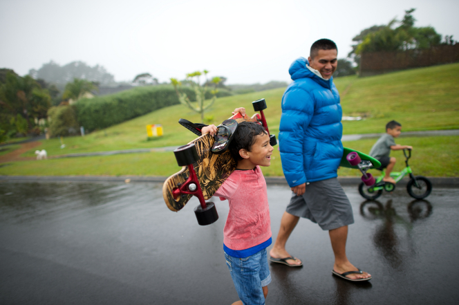 A father plays with two sons outside in the rain. One is skateboarding; the other son is riding a bike.