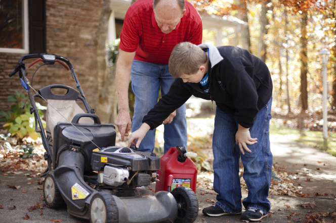 A father teaches his son how to use a lawn mower by pointing out different parts.