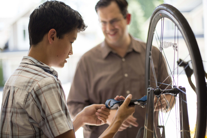 A young man fixes a wheel on a bike while his father stands nearby and helps him.