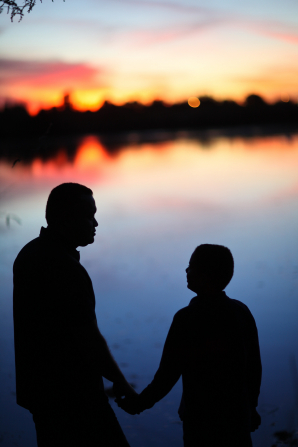 A silhouette of a father and young son holding hands near the water.