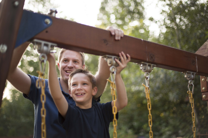 A father and son smiling while working on a wooden swing set with yellow chains.