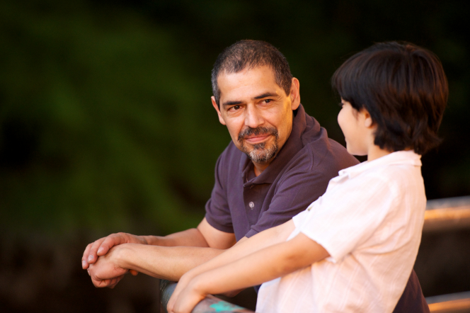 A father leans against a rail while talking with his son, who is next to him.