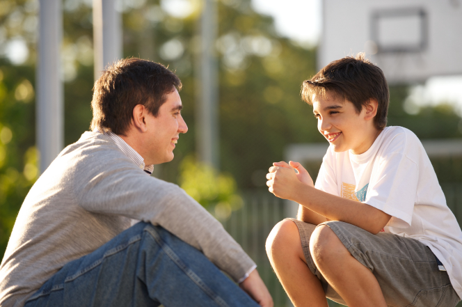 A father and son sit outside together and talk.
