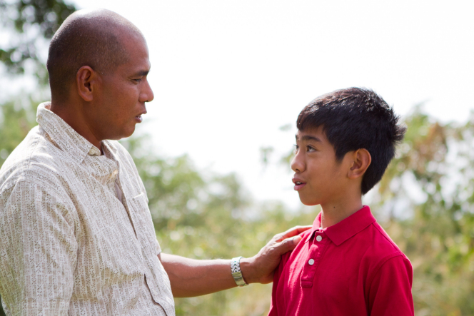 A father puts his hand on his son's shoulder and talks to him.